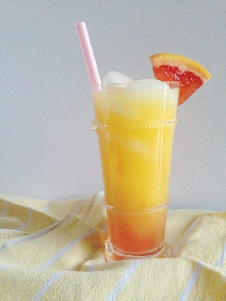 This Sweet Sunrise mocktail is a nonalcoholic play on the infamous Tequila Sunrise. Simply omit the tequila and add pineapple juice orange juice with a dash of orange bitters for more flavor. | Easy Mocktail Recipe | Brunch Drink | Brunch Mocktail | Pineapple Orange Drink | #drink #mocktail #speckledpalate