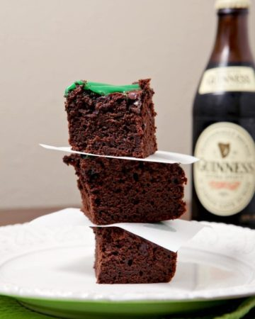 A stack of three brownies sits on a white plate in front of a bottle of Guinness beer