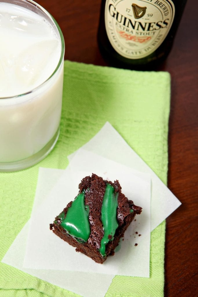 A Guinness Brownie with green frosting sits on a white napkin on top of a green towel next to a glass of milk