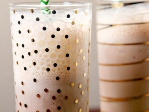Close up of two glasses holding milkshakes with green straws