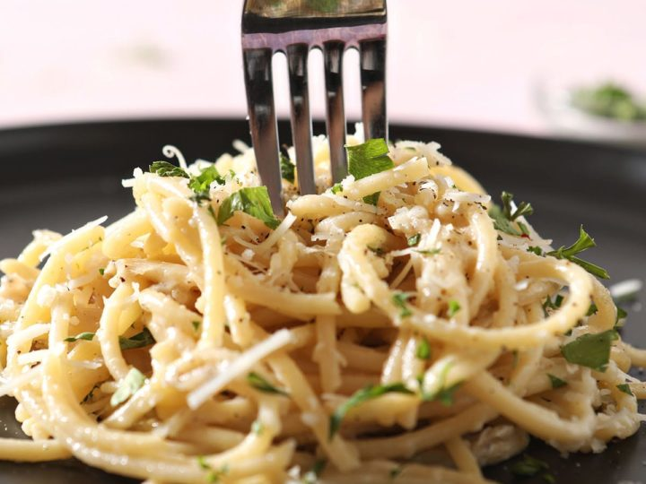 A fork twirls in a stack of pasta