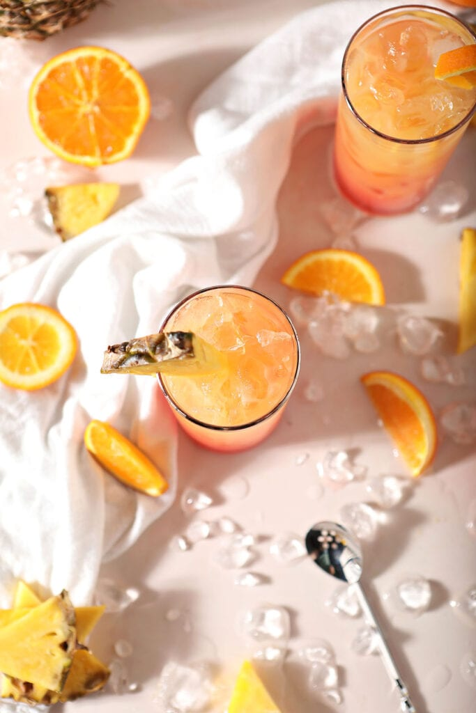 Two glasses holding orange drinks with oranges and pineapples around them
