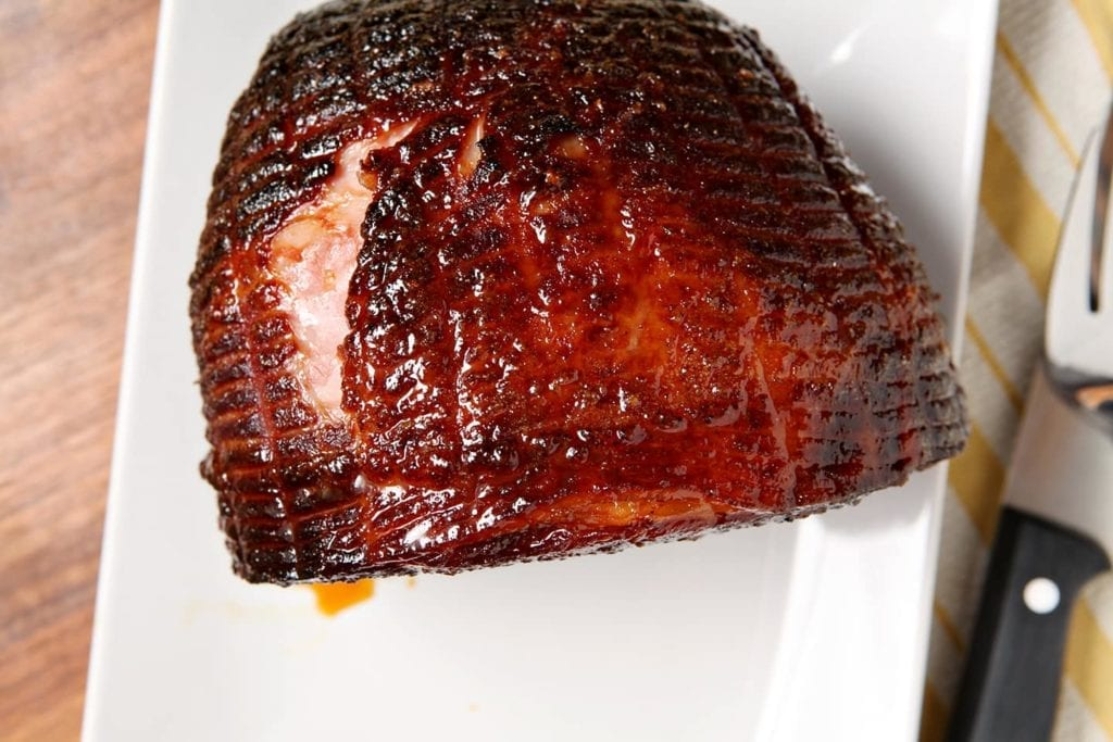 A whole glazed ham on a white platter, before slicing, from above