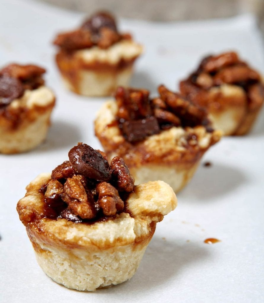 Celebrate the Kentucky Derby this coming weekend in style with Mini Bourbon Chocolate Pecan Pies! Bourbon, chocolate and pecans make for a delightfully sweet filling inside a cream cheese crust. Paired with bourbon, these mini pies are the perfect Derby Day sweet!