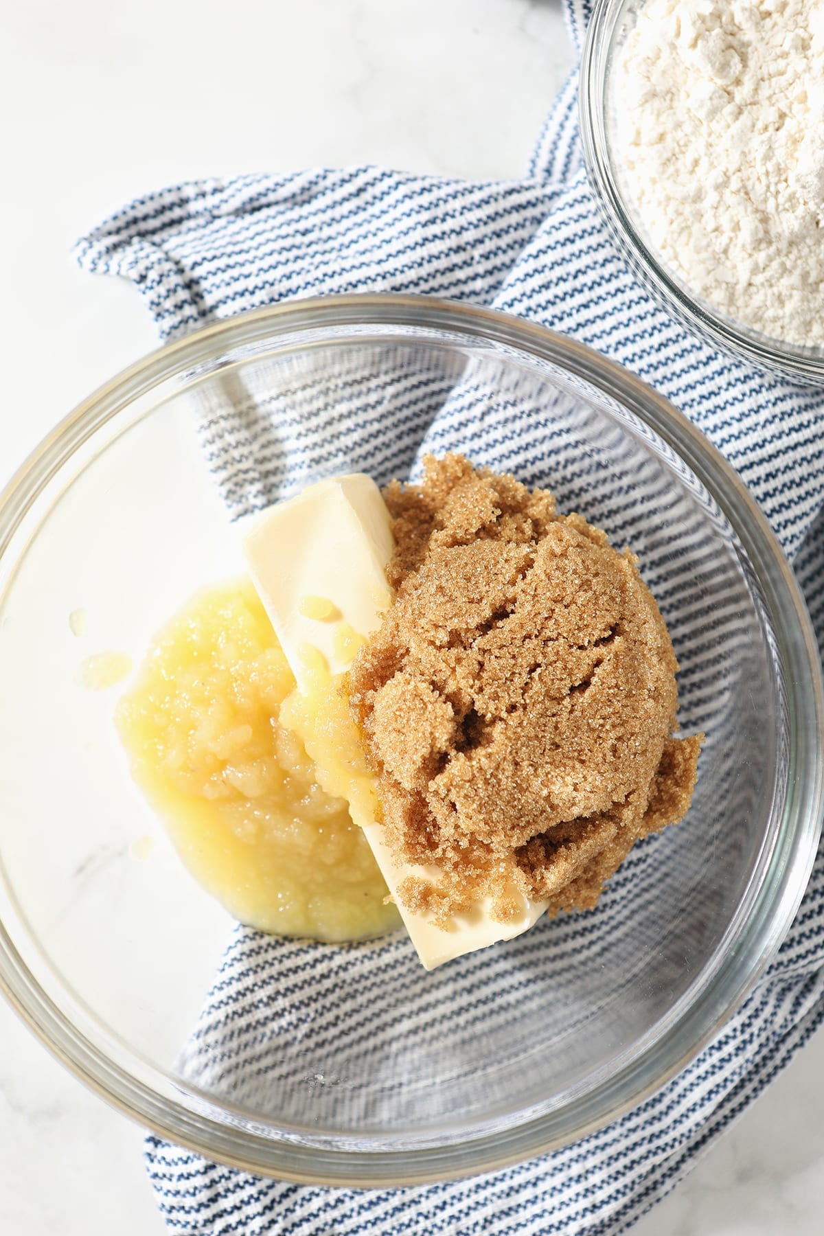 Butter, applesauce and brown sugar in a clear glass bowl on a blue striped towel