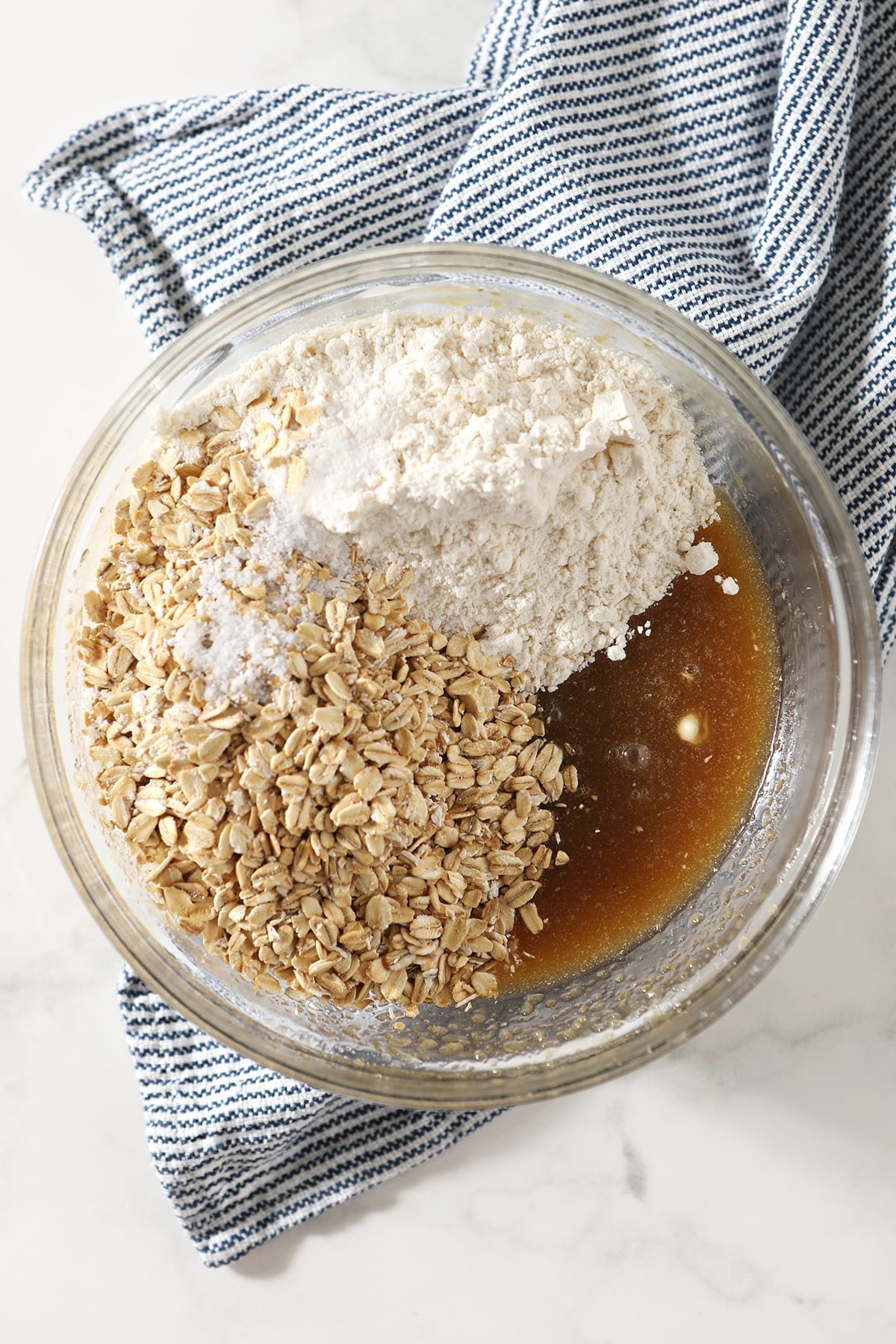 Rolled oats, flour and salt sit on top of the wet ingredients for the crust in a clear glass bowl on top of a blue and white striped towel