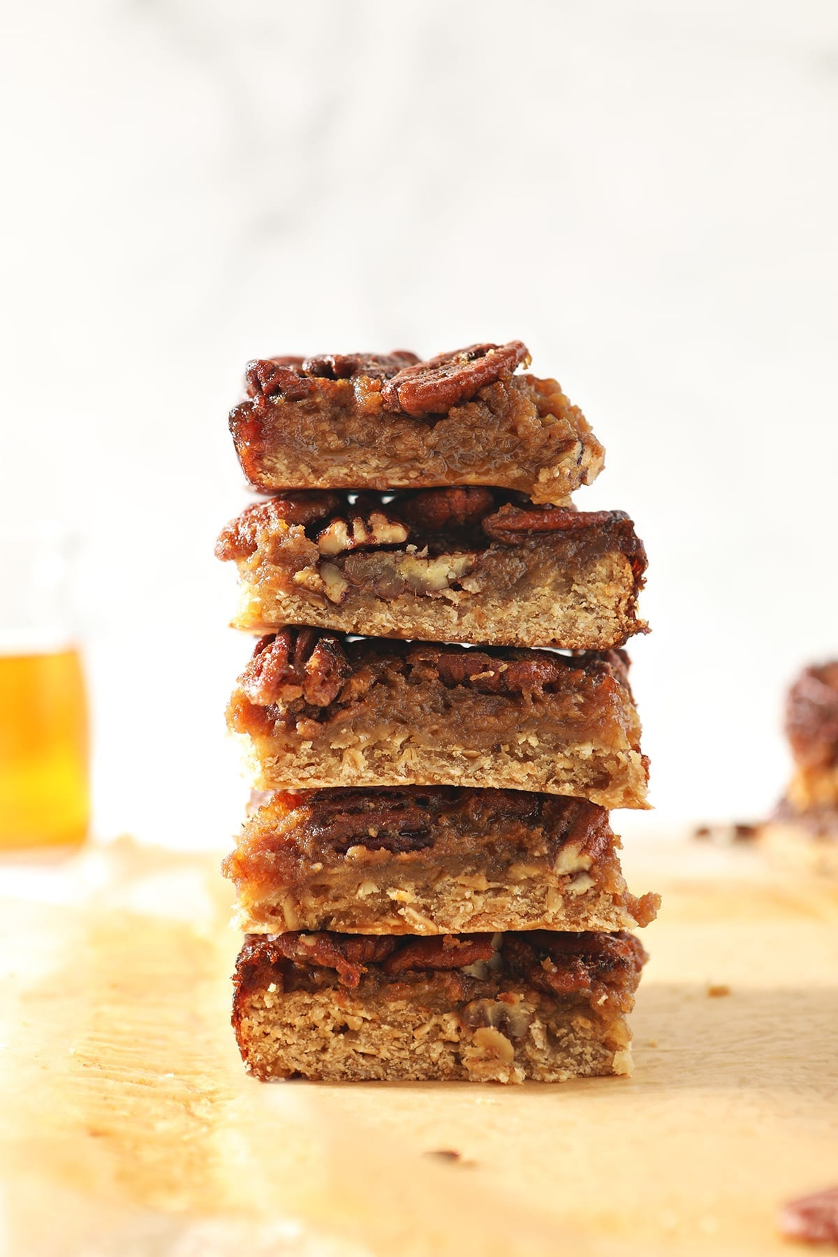 A stack of Bourbon Pecan Pie Bars in front of a vessel holding bourbon