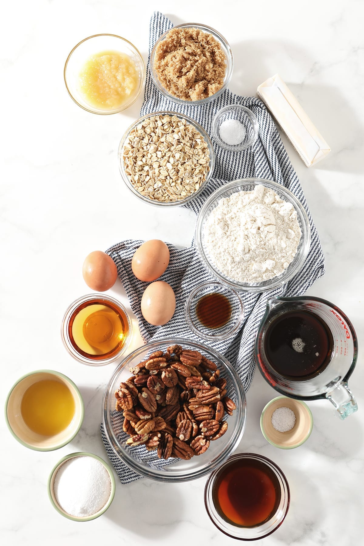 Ingredients to make Bourbon Pecan Pie Bars and their in bowls on top of a blue and white striped towel