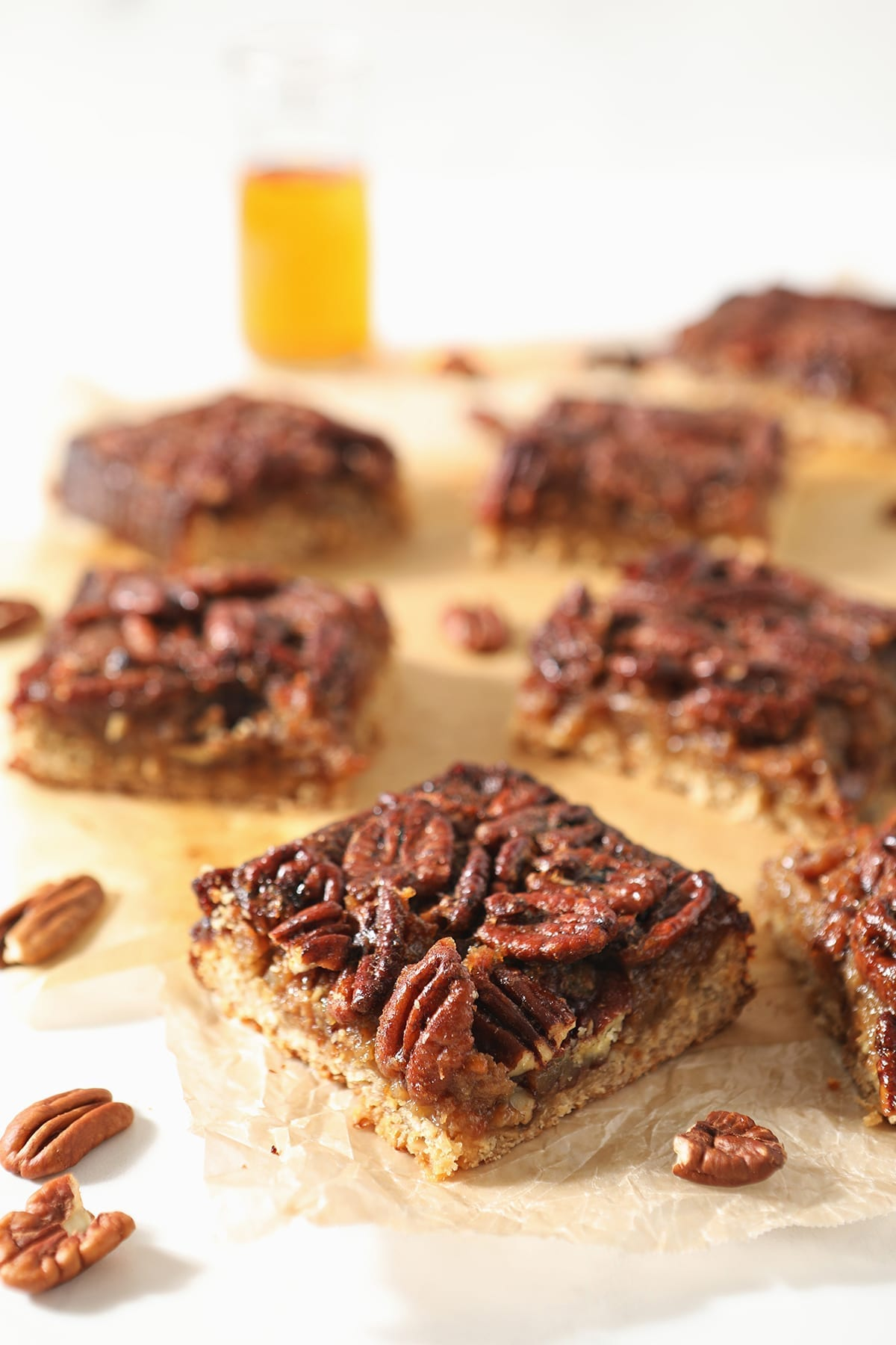Sliced Bourbon Pecan Pie Bars sit on wax paper with a cup of bourbon behind them