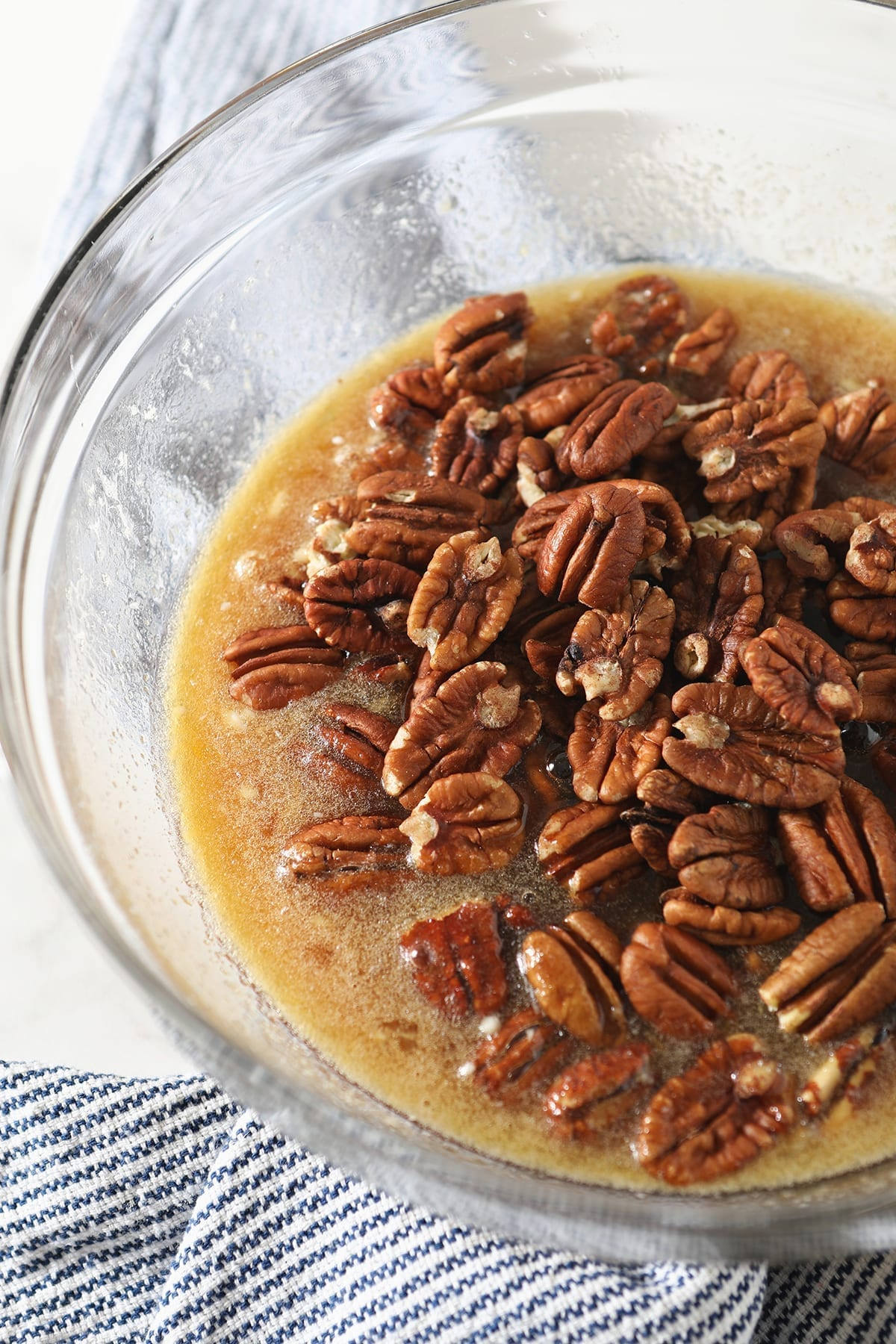 Pecan halves sit on top of other filling ingredients in a clear glass bowl