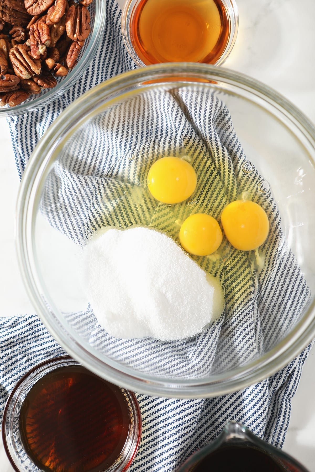Overhead view of sugar and three broken eggs in glass bowl