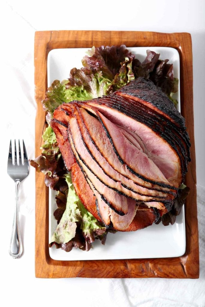 A whole honey roasted ham on a white platter on top of greens before eating