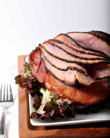 A homemade Honey Ham on a wooden platter, served on a white dish, ready for eating.