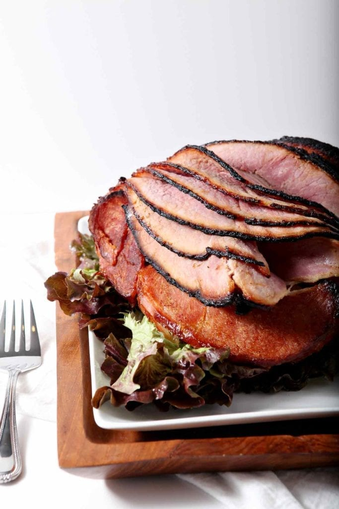 Honey Ham on a wooden platter, served on a white dish, ready for eating.
