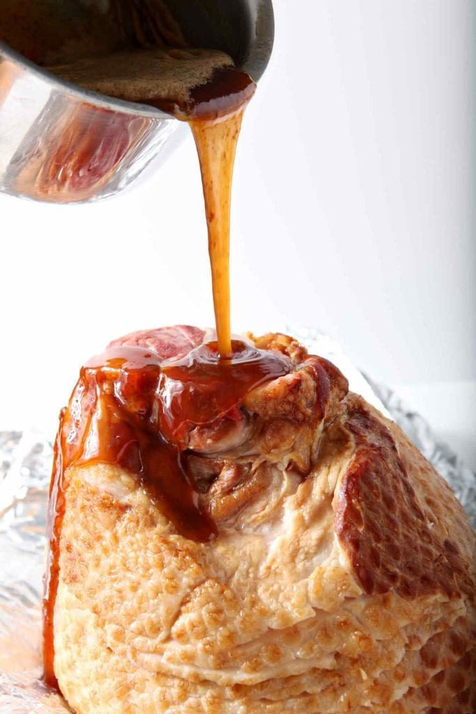 Honey glaze being poured on a ham before baking