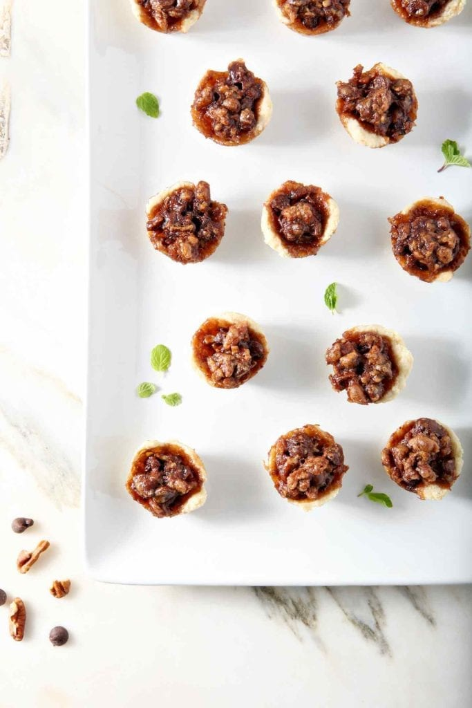 Mini Bourbon Chocolate Pecan Pies, after baking, on a white platter.