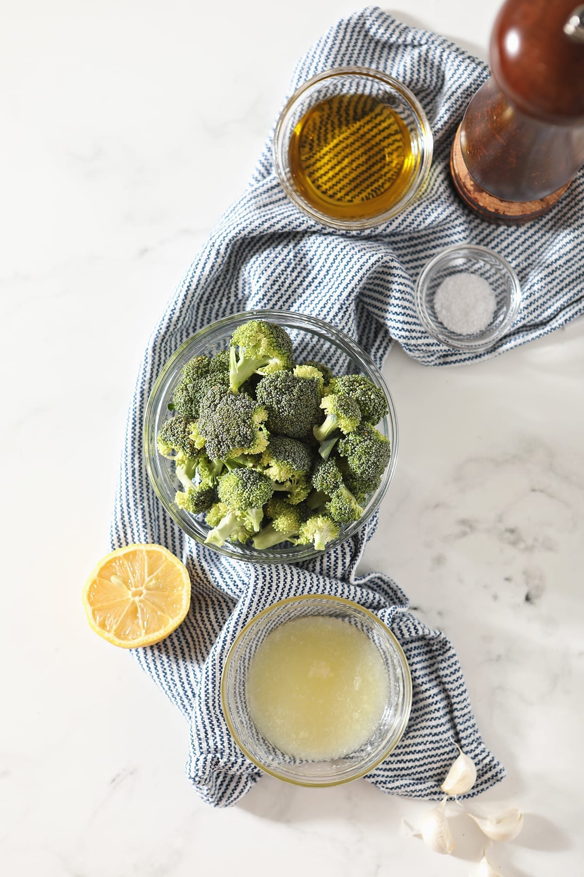 Broccoli, lemon juice, salt, pepper and oil are shown in bowls on a blue and white striped towel on marble