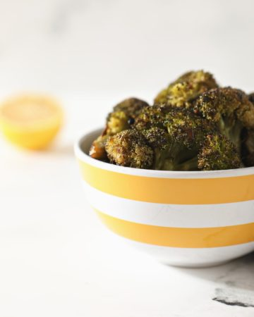 Roasted Broccoli with Lemon and Garlic in a yellow and white striped bowl sitting on a marble counter