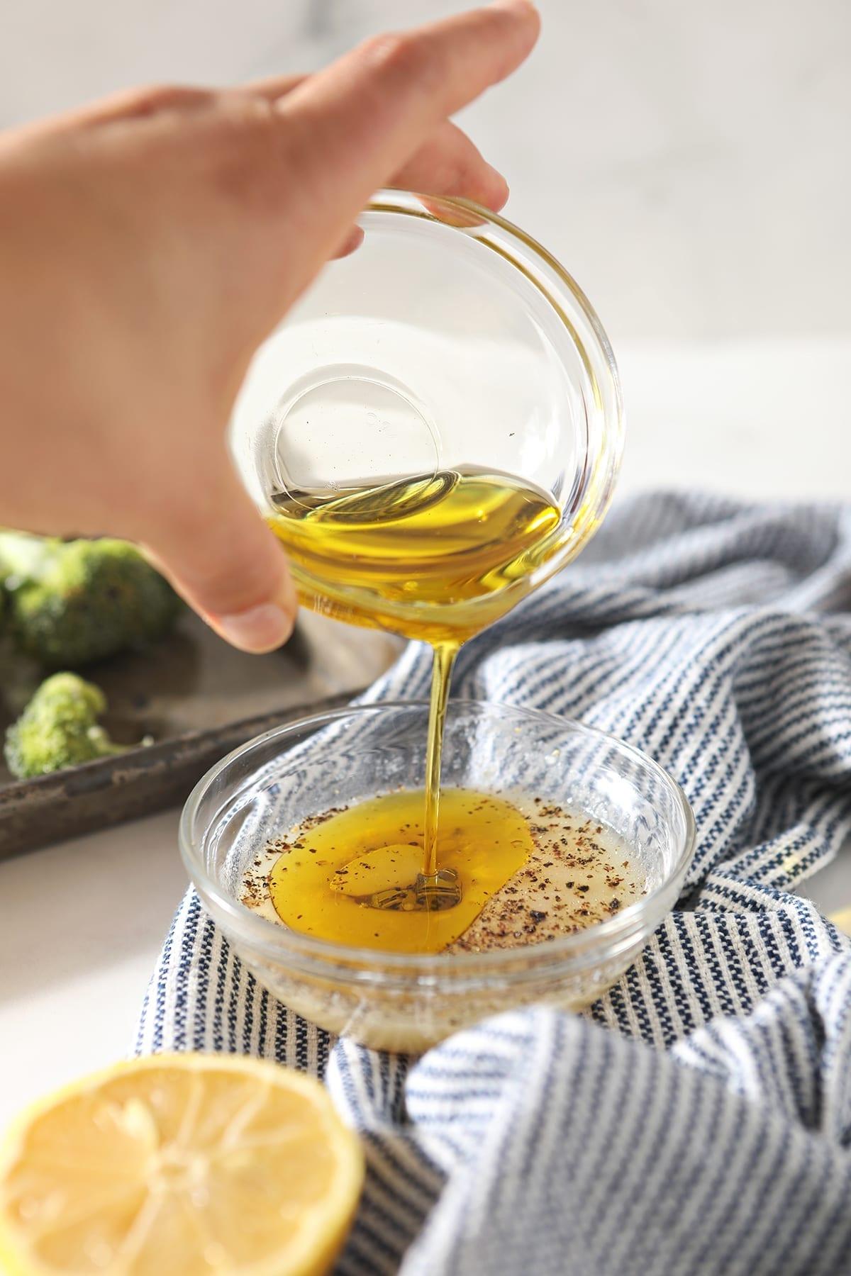 Oil pours into a lemon juice mixture in a clear glass bowl