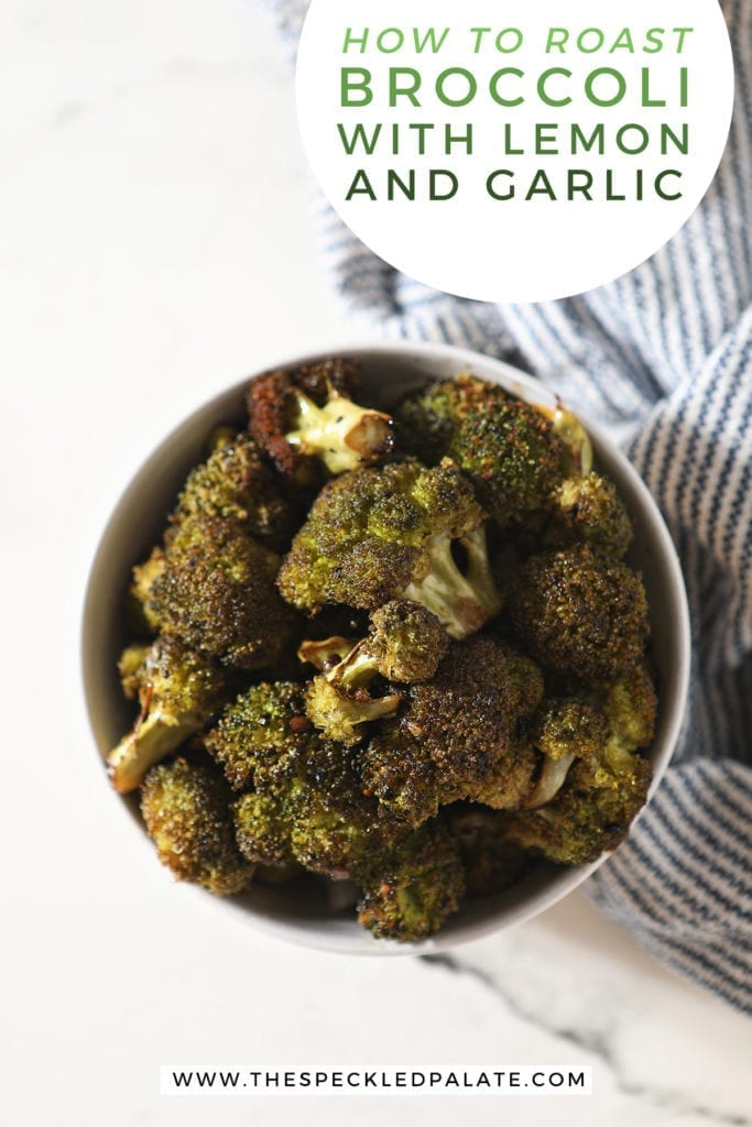 Roasted Broccoli in a bowl sitting on top of a blue and white striped towe with the text 'how to roast broccoli with lemon and garlic'
