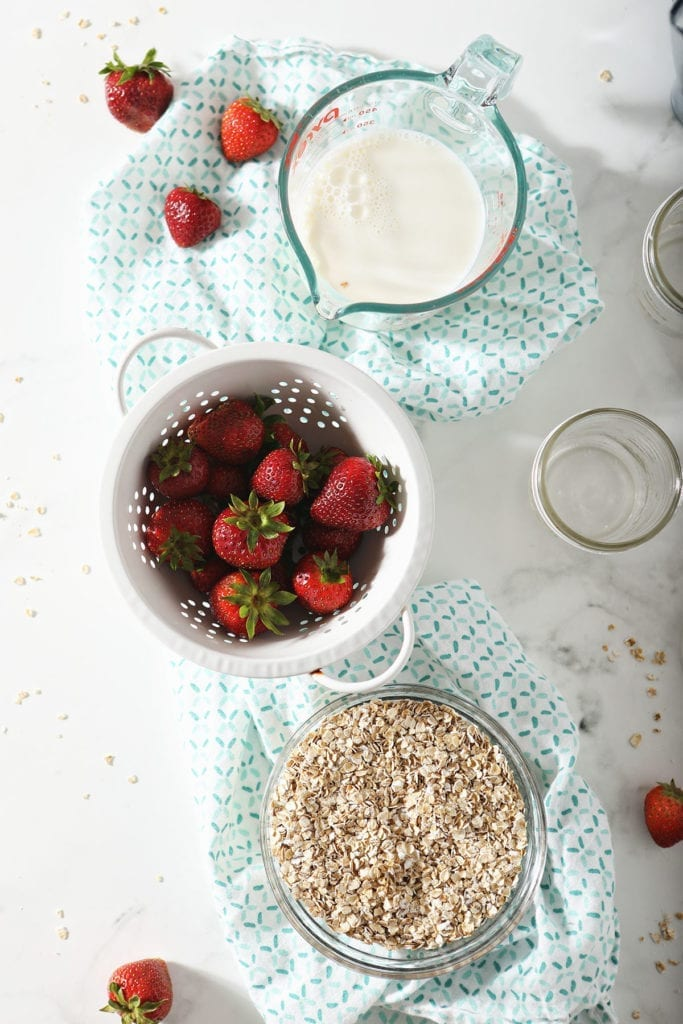 Fresh strawberries, oats and milk on a turquoise patterned towel next to mason jars