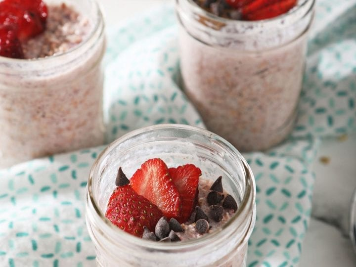 Four containers of strawberry overnight oats sit on a turquoise kitchen towel, garnished with strawberries and other ingredients
