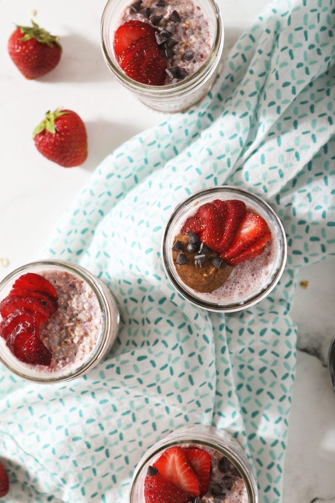 Four servings of strawberry overnight oats in mason jars, garnished with strawberries, almond butter and chocolate chips