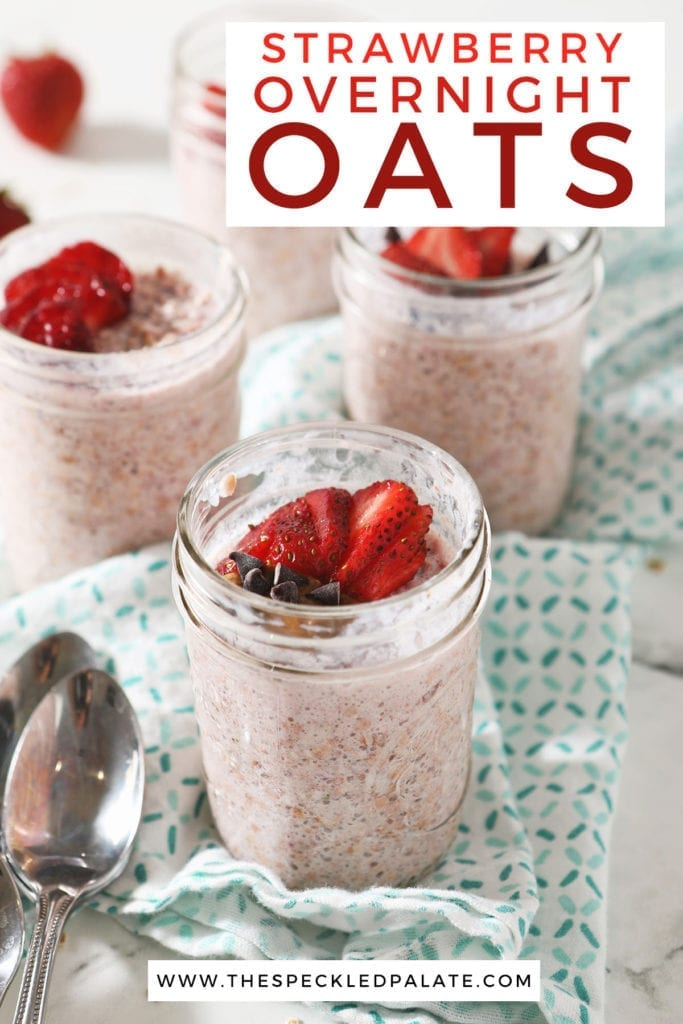 Four mason jars of overnight oats sit on a turquoise kitchen towel, garnished with strawberries and other ingredients with the text 'strawberry overnight oats'
