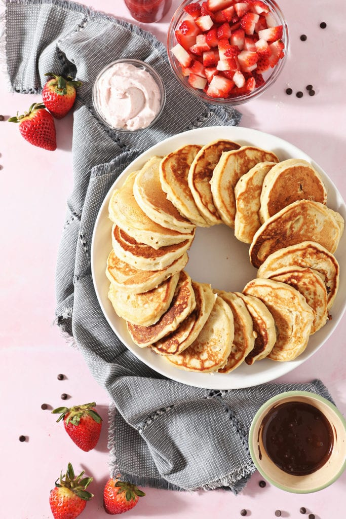Old Fashioned Pancakes in a ring on a plate next to strawberries and a chocolate sauce
