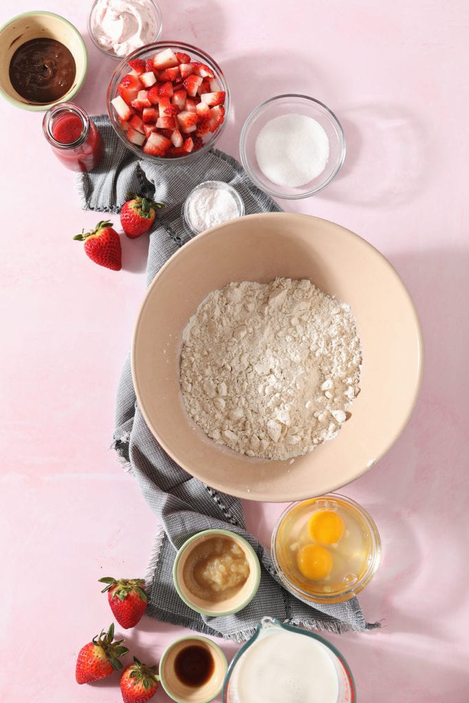 Ingredients to make pancakes with strawberries on a pink background