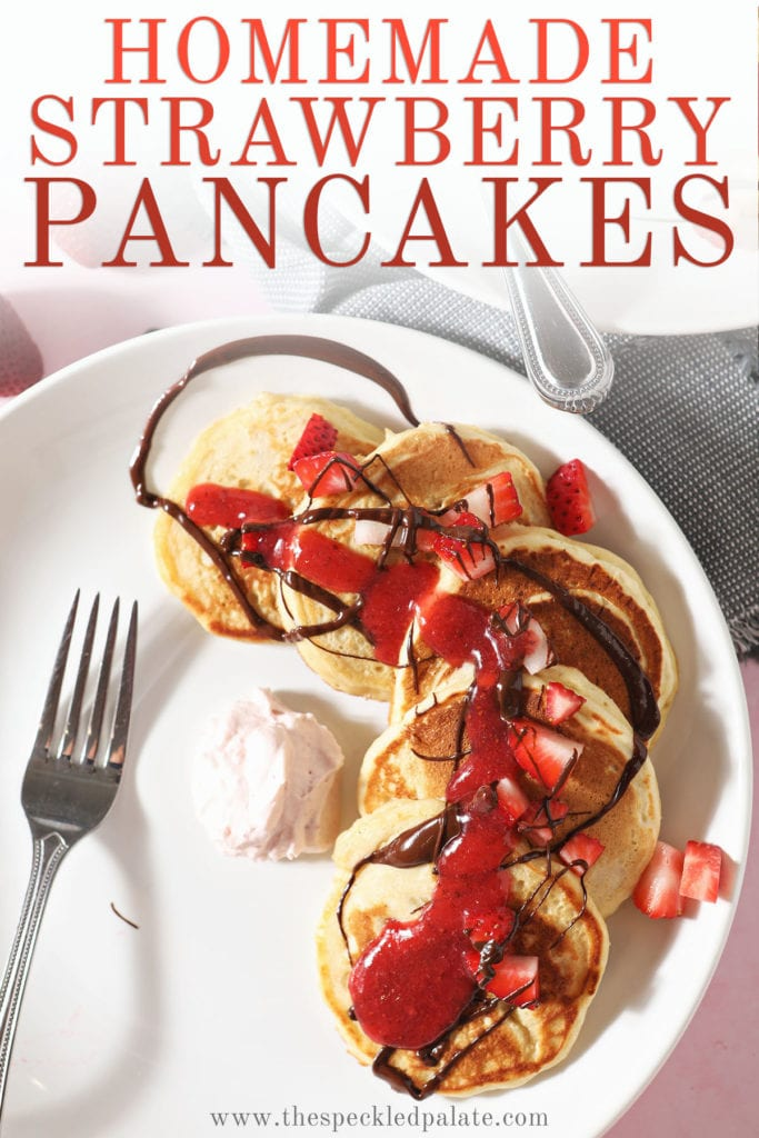 Pancakes topped with strawberries, chocolate and strawberry sauce with the text 'homemade strawberry pancakes'