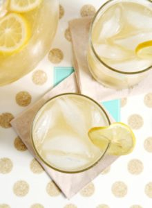 Overhead image of two glasses of lemonade next to a pitcher sitting on a gold and white polka dot platter on a blue tabletop