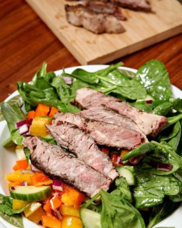 A plate of food on a table, with Salad and Steak