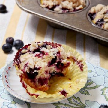 Dairy-Free Blueberry Lemon Crumble Muffin sits on a patterned blue napkin, with additional muffins in a tin and blueberries in the background