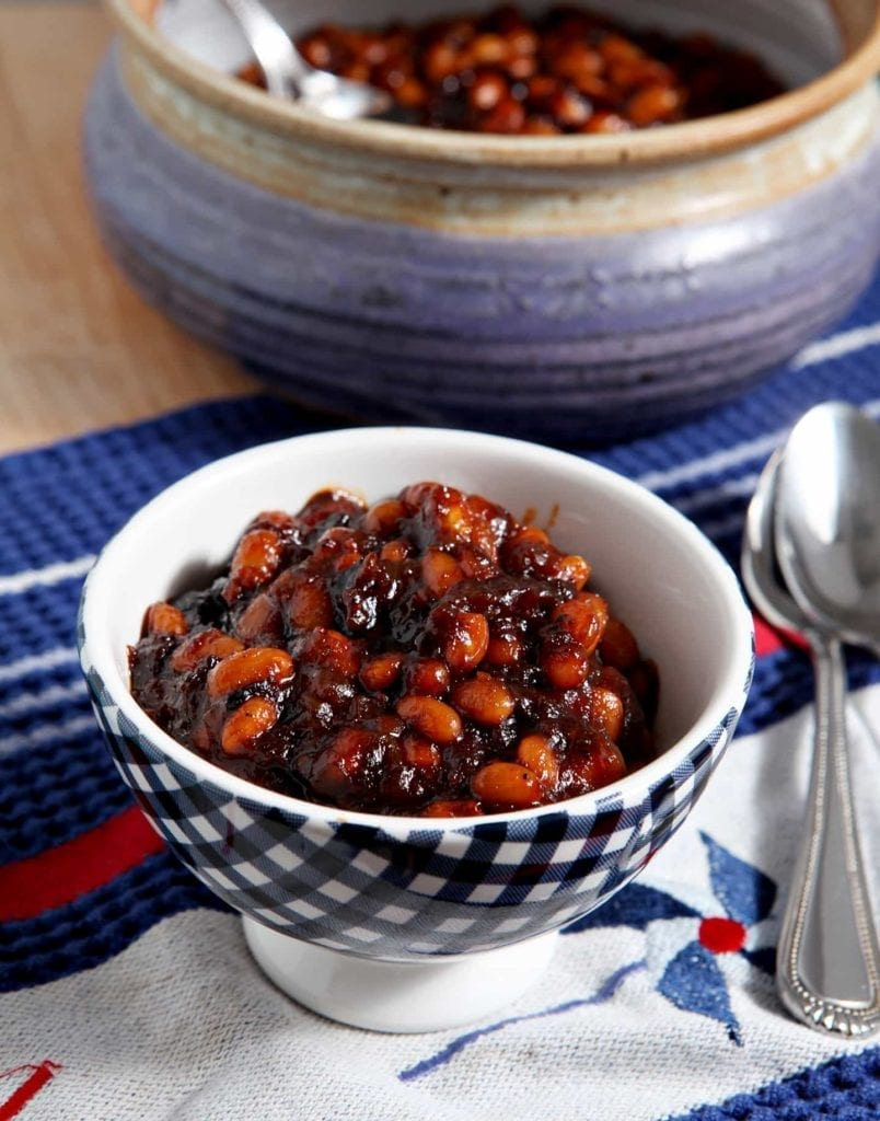A bowl of spicy baked beans sits next to a bean pot