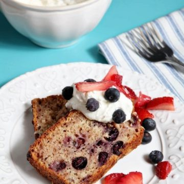 Two slices of Berry Pound Cake, topped with homemade whipped cream and fresh berries, sit on a white plate on a turquoise background