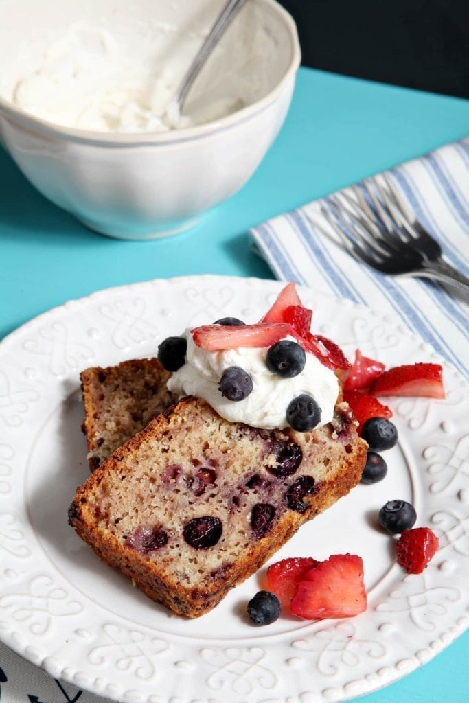 Two slices of Berry Pound Cake are stacked on top of each other on a plate with whipped cream and berries.
