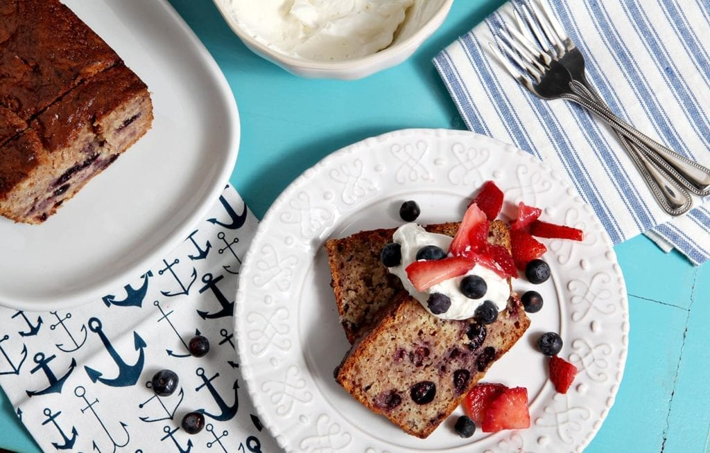 Two slices of berry pound cake are served with homemade whipped cream, blueberries and sliced strawberries