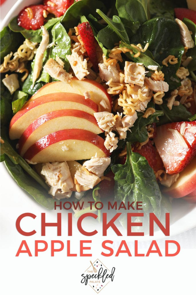 Apples, strawberries and chicken on a spinach salad with the text 'how to make chicken apple salad'