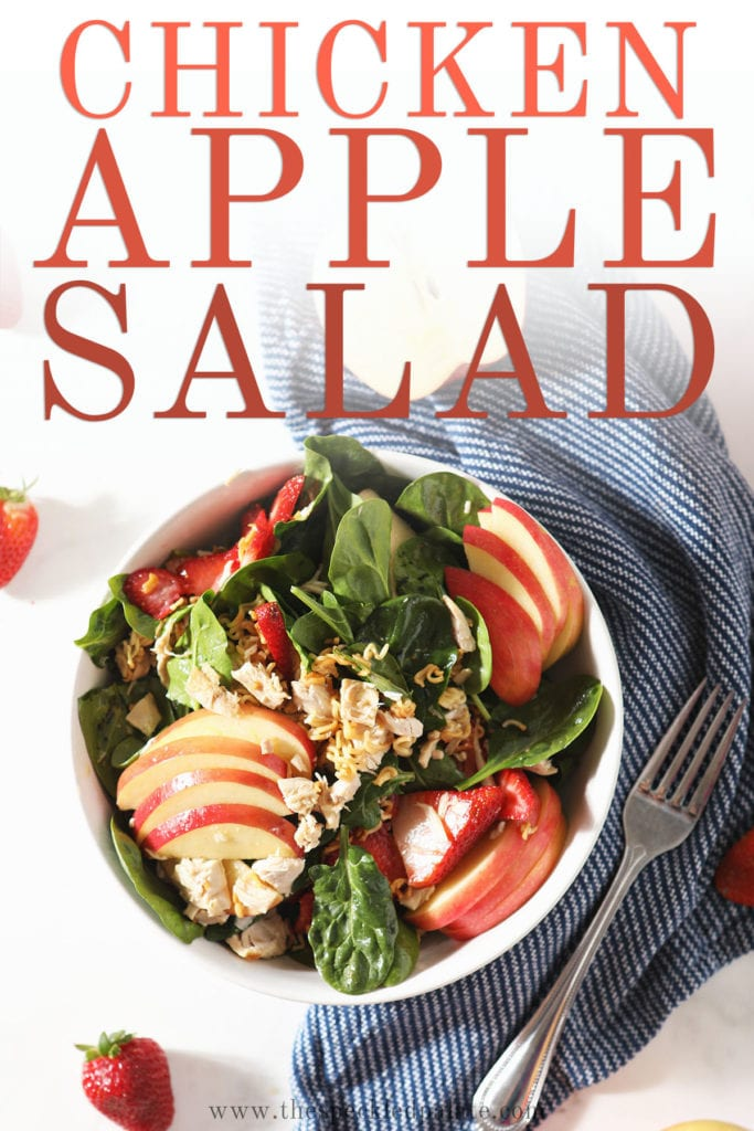 A bowl of chicken spinach salad on marble with the text 'chicken apple salad'