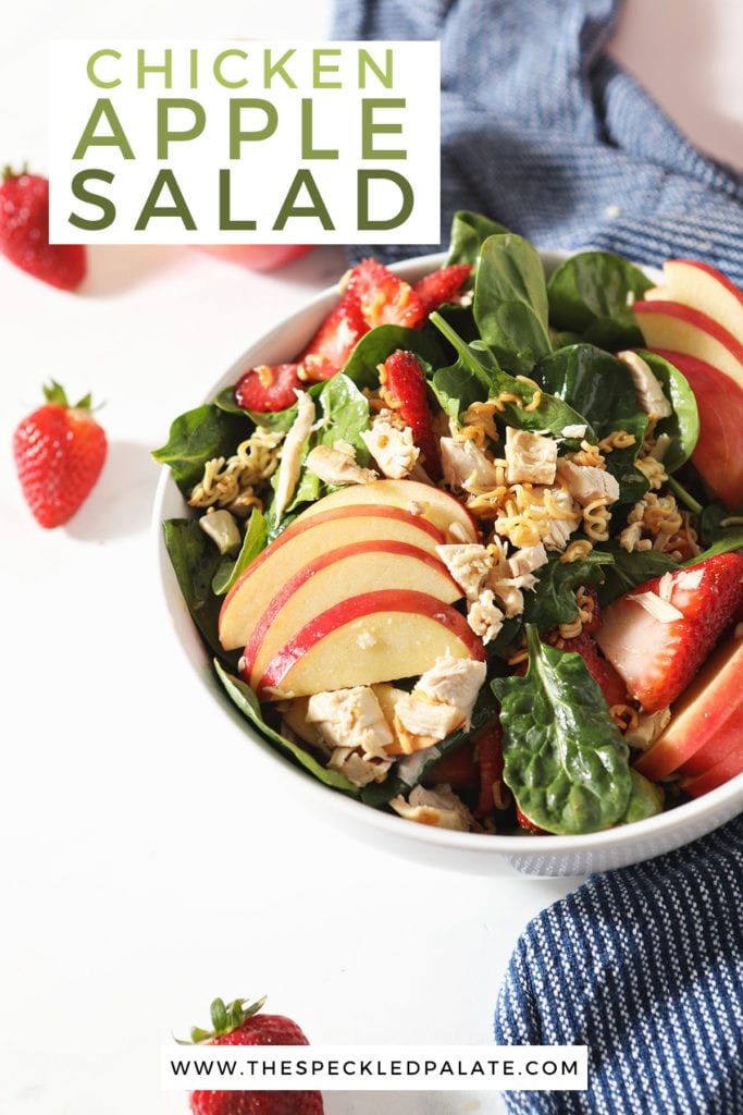 A bowl of a fruit and spinach salad with the text 'how to make chicken apple salad'