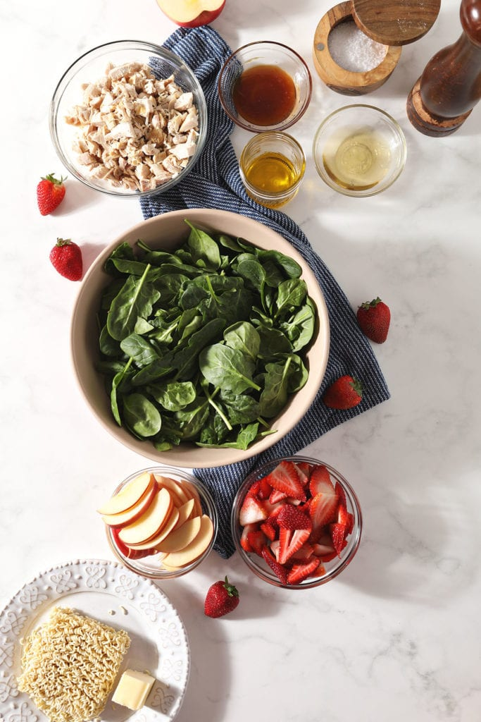 Ingredients for a spinach salad with chicken in bowls on marble