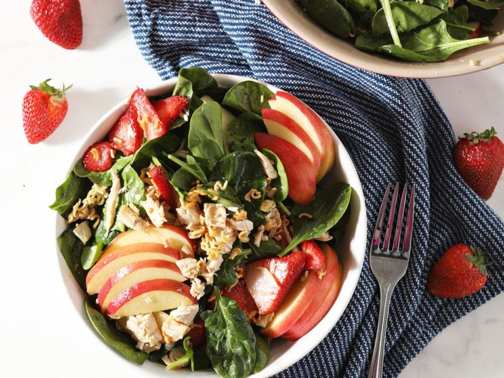 Two bowls of Chicken Spinach Salad with a blue napkin