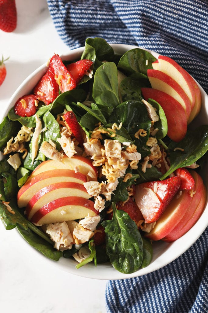 Apples, strawberries and chicken on a spinach salad