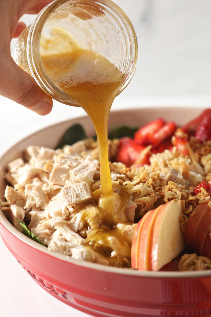 Honey vinaigrette pours on top of a chicken spinach salad with fruit
