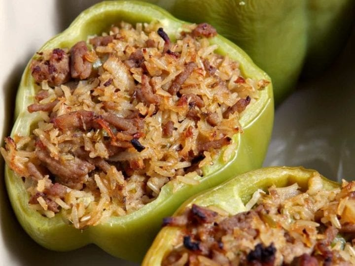Three Turkey Jambalaya Stuffed Bell Peppers sit inside a baking dish after cooking.