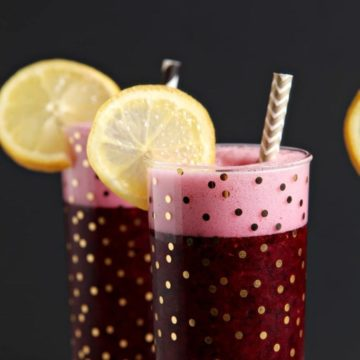 Three glasses of deep purple-colored Spiked Blueberry Lemonade sit together in front of a black background