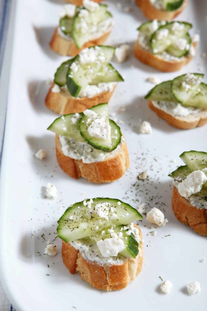 Cucumber Bruschetta sits on a white platter, garnished with additional feta cheese and dill