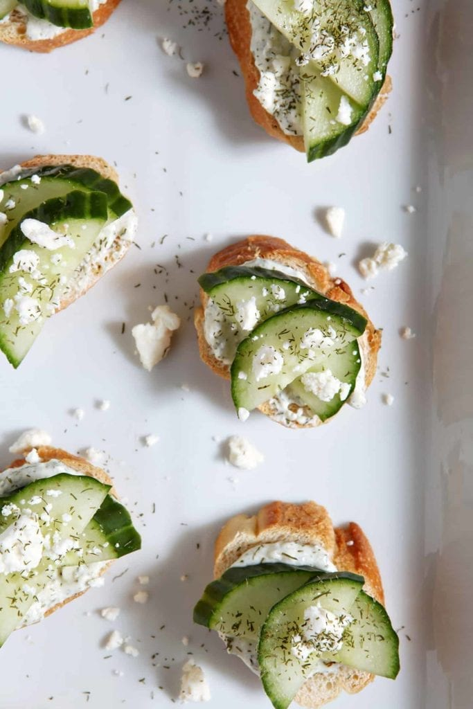 Overhead of Cucumber Bruschetta sitting on a white platter, garnished with additional feta cheese and dill