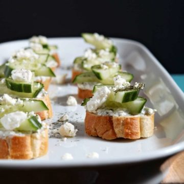 Cucumber Bruschetta, served on a white platter, sits on a wooden background and is ready for enkoying